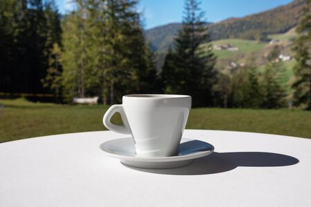 White cup of coffee in outdoor setting. Summer oudoor coffee break