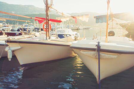Sunny landscape with fishing boats and yachts in marina harbor of Mediterranean city. Budva, Montenegro