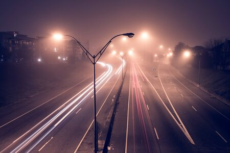 Highway at foggy night with bright trails of light from incoming and outgoing traffic. Transportation, traffic, urbanism and infrastructure concepts. Stockfoto