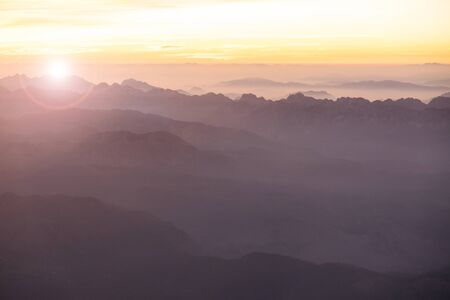 Foggy morning in Italian Alps mountains. Mountain range silhouttes aerial view.