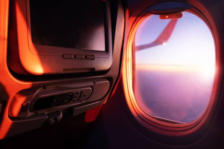 Seats, TV system and window inside an aircraft. Airplane interior in sunlight Stockfoto