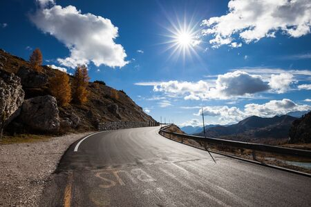 Road in mountain valley at sunny morning in Dolomites, Italy. View with asphalt roadway, meadows, mountains, blue sky with clouds and sun. Highway in mountain. Trip in europe. Travel Stockfoto
