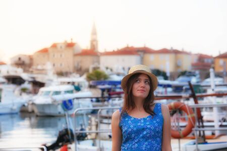 Europe summer travel mediterranean destination. Tourist woman on vacation, walking on the streets of old and beautiful Mediterranean city in hat and summer dress Stockfoto