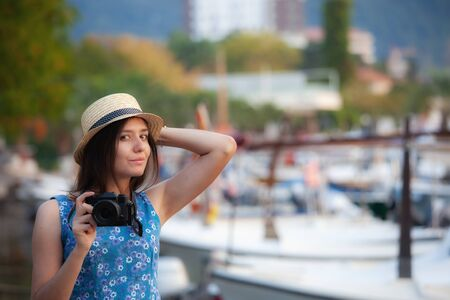 Young attractive cheerful travel girl walking with camera in old Mediterranean city. Summer travel concept. Budva, Montenegro Stockfoto