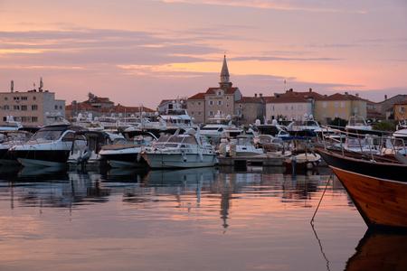 Budva bay sunrise. Panoramic view of marina, boats and old city. Montenegro