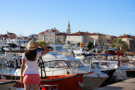 Europe summer travel mediterranean destination. Tourist woman on vacation, walking on the marina of old Mediterranean city. Budva, Montenegro Redactioneel