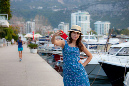 Young travelling woman in hat taking selfie photos over summer sunny mediterranean city with smartphone camera. Brunette girl making photography on summer vacation