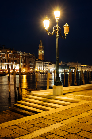 Venice canal with historical buildings and gondolas at night. Italy.