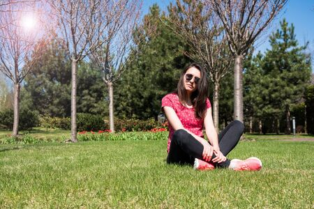 Cute long-haired girl sitting on the green lawn and looks to the side. Girl in the city spring park