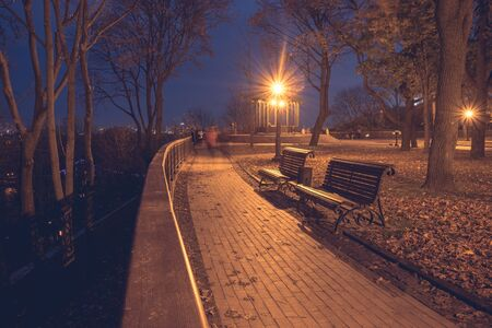 Night city park. Wooden benches, street lights and park alley Stock Photo