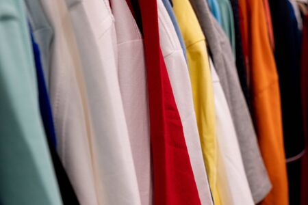Row of colorful t-shirts on shoulders hangers in retail shop