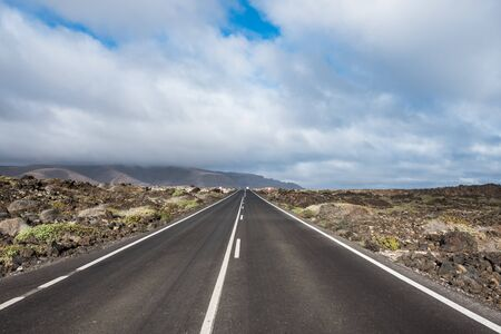 Endless road to Timanfaya National park in Lanzarote, Canary Ispands, Spain, Europe, Africa. Volcanic, black sand, harsh, tough, inhospitable, dry, sub-tropical, desert landscape.
