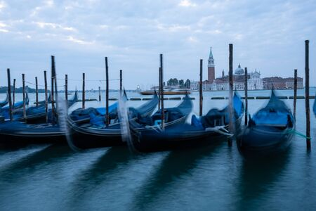 Gondolas moored by Saint Mark square with San Giorgio di Maggiore church in Venice, Italy