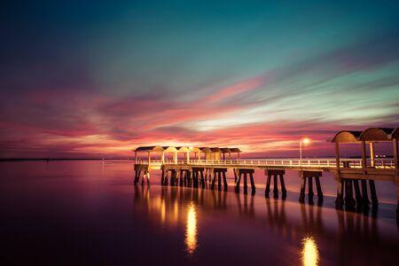 A beautiful ocean dramatic sunset and fishing pier at Jekyll Island in coastal Georgia, USA. Stok Fotoğraf