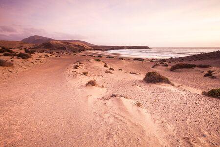 Sand desert dunes and sea beach landscape at sunrise