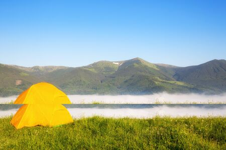 bright yellow tourist tent in the mountains nature