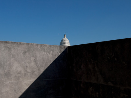 United States capitol behind bold concrete wall and shadow
