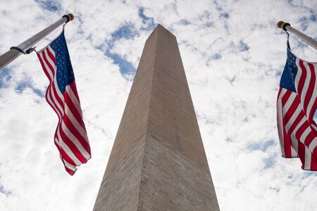 Washington Monument on a cloudy day with American flags flapping in the wind