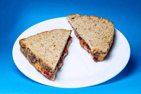 Peanut butter and jelly sandwich made with whole grain bread, natural peanut butter, and jelly on a white glass plate with a blue background
