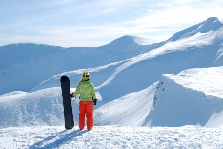 Girl with Snowboard at the mountains photo