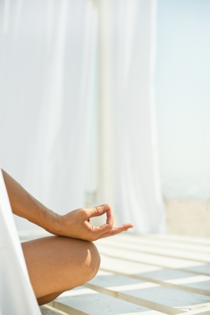 sexual chakra: Woman meditating on beach in lotus position Stock Photo