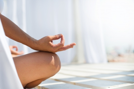Woman meditating on beach in lotus position Stock Photo