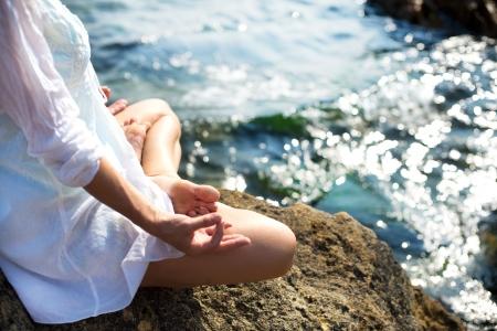 Woman meditating on beach in lotus position Archivio Fotografico