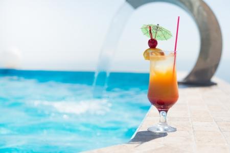 infinity pool: The orange cocktail near the swimming pool Stock Photo