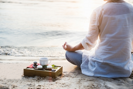 Woman meditating at the beach and drink tea Stock Photo