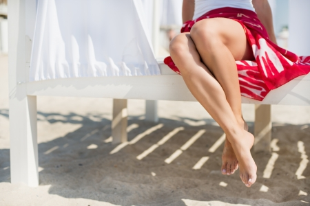 Womans legs at beach at sunny day