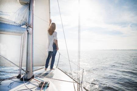 vrouw verblijft op de zeilboot tijdens zonsondergang