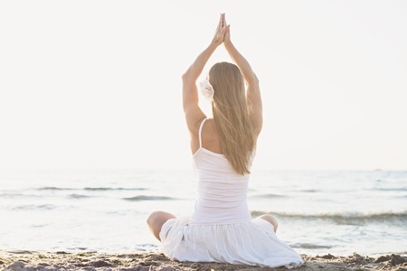 Young blonde woman meditation on the beach Stock Photo