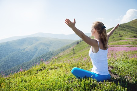 Young woman meditate on the top of mountain  photo