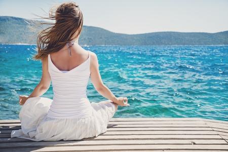 Vrouw mediteren bij de zee Stockfoto