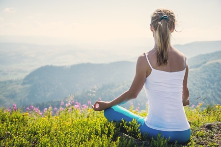 Young woman meditate on the top of mountain Stock Photo