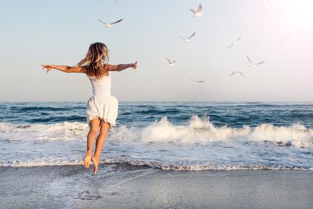 Beautiful girl  jumping on sea