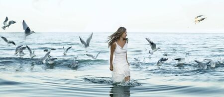beautiful woman and seaguls on the beach photo
