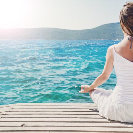 mujer meditando: Mujer meditando en el mar