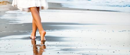 piernas mujer: Mujer que camina en la playa de arena Foto de archivo