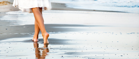 young woman legs up: Woman walking on sand beach