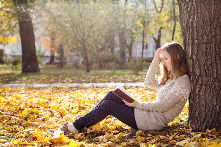 Young beautiful woman reading a book at the park