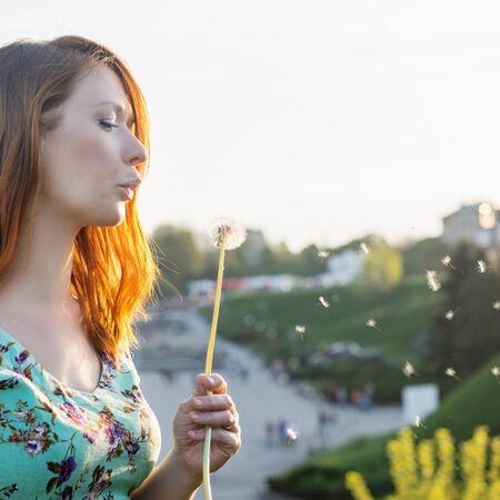 dandelion field: Beutiful women blowing the dandelion at the park