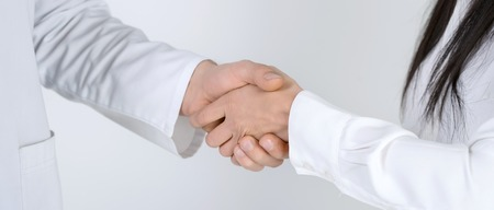 physiotherapy: Close up of patient shaking hands with doctor