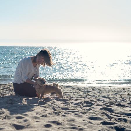 sexy young girl: женщина, играя со своей собакой на пляже во время восхода солнца