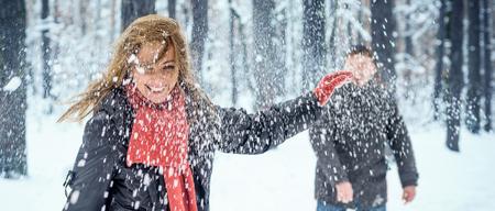women fight: Winter couple having fun playing snowball fight