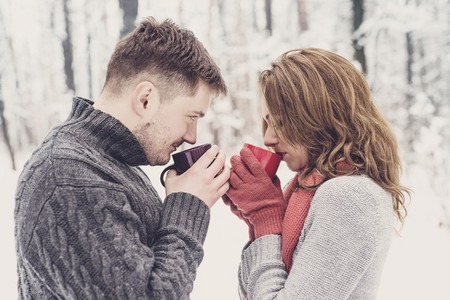 romantic date: Happy couple drinking tea together outdoors in winter Stock Photo