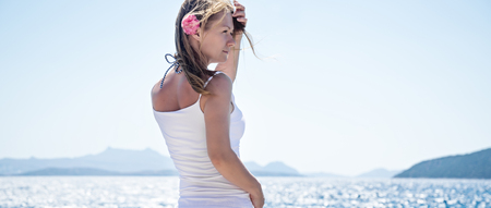 Beautiful blonde girl standing at the sea Stock Photo