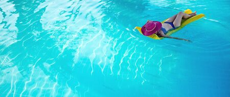 clear water: Young woman in hat enjoying a swimming pool Stock Photo