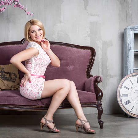 woman couch: Beautiful luxurious woman on a vintage couch Stock Photo