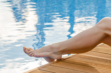 Female legs on the wooden deck in the pool water Stock Photo